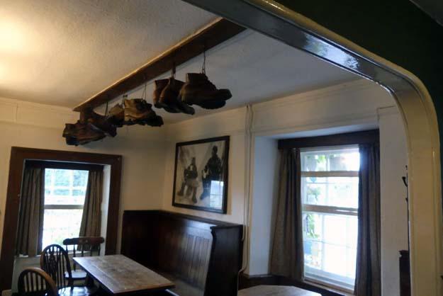 Une salle de l'hôtel Pen-Y-Gwyrd avec les vieilles chaussures de randonnée des alpinistes anglais